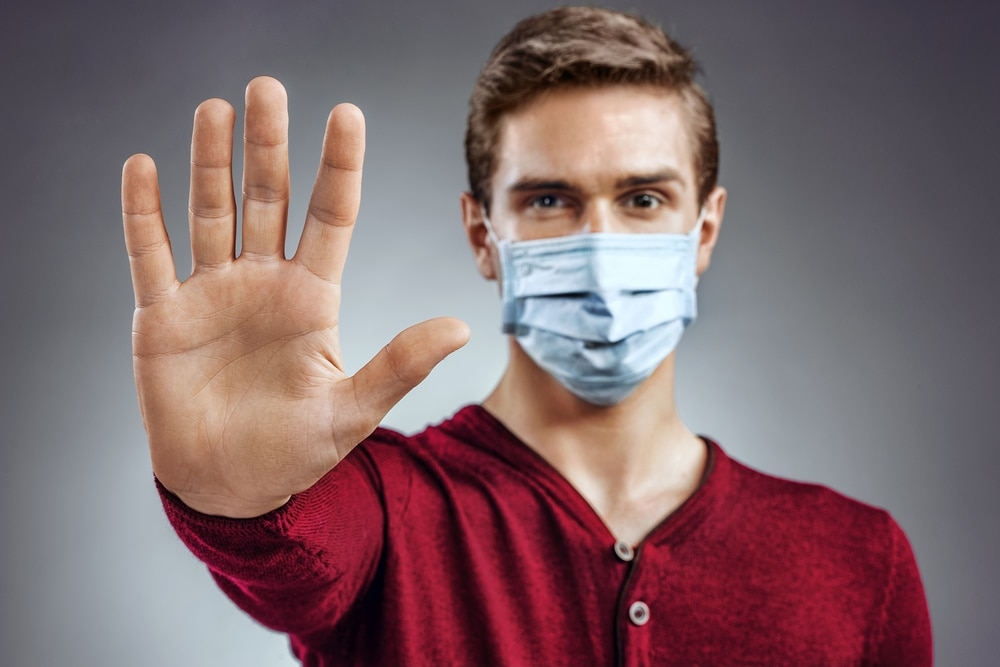 Man wearing face mask with hand out in front